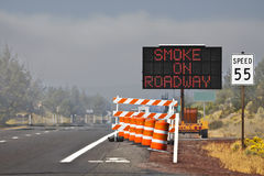 Smoke On Roadway Sign Barricade. On the road near a forest wildfire the warning signs were put up to warn drivers about the smoke on the roadway Stock Images