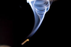 Smoke shapes from aromas incense. Black background with blue shapes Royalty Free Stock Photography