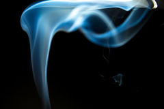Smoke shapes from aromas incense. Black background with blue shapes Stock Photography