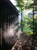 Smoke shed. A trail of smoke from behind the shed Royalty Free Stock Photo