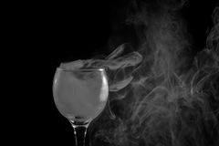 Smoke shisha in cocktail glass on a black background. Stock Photo