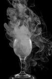 Smoke shisha in cocktail glass on a black background. Royalty Free Stock Images