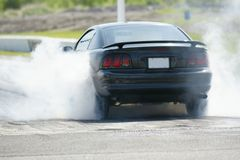 Smoke show. Picture of mustang burning rubber during drag race royalty free stock image