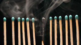 Smoke of single burned matchstick between row of new matchsticks Royalty Free Stock Photography