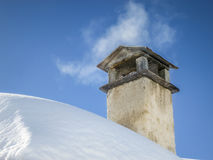 Smoke spreading from chimney on snowy roof Royalty Free Stock Images