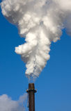 Smoke Stack. Factory chimney billowing smoke against a blue sky Royalty Free Stock Photography