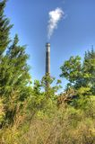Smoke Stack. With Smoke Framed by Natural Fresh Vegetation Royalty Free Stock Photography