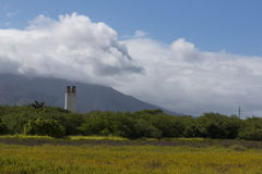 Smoke Stack Beyond A Field. A small smoke stack beyond a beautiful field in Maui, Hawaii, with a gorgeous mountain laying in the background Royalty Free Stock Images