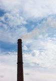 Smoke stack of the industrial plant against the cloudy sky Royalty Free Stock Photos