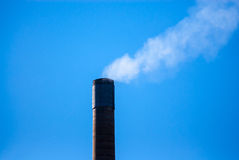 Smoke stack releasing white smoke on blue sky. Royalty Free Stock Photo