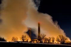 Smoke stacks in center. Horizontal color image of power plant smoke stacks and steam clouds at night Stock Photos