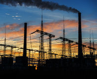 Smoke stacks at coal burning power plant, industrial silhouette. stock images