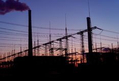 Smoke stacks at coal burning power plant, industrial silhouette. royalty free stock photography