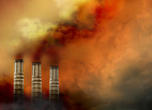 Smoke Stacks with Pollution Smoke. Three smoke stags have pollution smoke coming out of the tops and there is a lot of smoke surrounding them Stock Photo