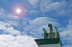 SMOKE STACKS OF SHIP WITH ADDED LENS FLARE. Smoke stacks of a ship against sky and clouds with added lens flare stock image