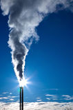 Smoke in the sun. Smoke from a chimney on a blue sky Stock Photography
