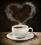 Cup of coffee. Cup of hot coffee with beans surrounding the saucer and  with hot vapor rising from it forming a heart shape against a dark background Stock Photo