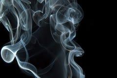 Smoke curls on black. Smoke swirls on black background royalty free stock photography