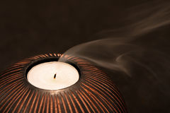 Smoke trails as a candle is extinguished. Smoke trails from a candle as its flame is extinguished. On a dark background, with short depth of field Royalty Free Stock Images