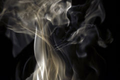 Smoke trails rising in white, gray and brown wisps Stock Image