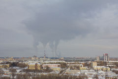 Smoke tubes in skyline - Industrial landscape at winter snow city Stock Photos