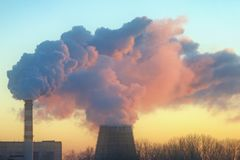 Smoke from two factory chimneys in the light of the setting sun. Stock Images