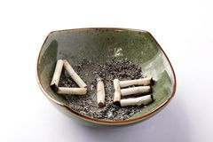 Smoke untill you die. Die written on a dirty ashtray with cigarettes Stock Photos