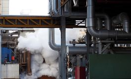 Smoke, vapor, pipes, tubes and valves in a factory Stock Images