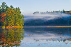 Smoke on the Water. Misty autumn morning lake with a smoke hanging above the water Royalty Free Stock Photo