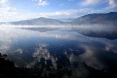 Smoke on the Water. Smoke floats across a mountain lake stock photos