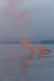 Smoke on the water. Orange emergency flare smoke on the water Royalty Free Stock Photos