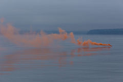 Smoke on the water. Orange emergency flare smoke on the water Stock Images