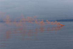 Smoke on the water. Orange emergency flare smoke on the water royalty free stock photography