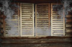 Smoke from wooden house windows Stock Photo