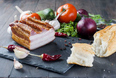 Smoked bacon with baguette and vegetables on stone black board Royalty Free Stock Photography