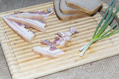 Smoked bacon, bread, green onion on a wooden cutting board Stock Photos