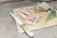 Smoked bacon, bread, green onion on a wooden cutting board Stock Image
