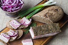 Smoked bacon with onion and rye bread Stock Images
