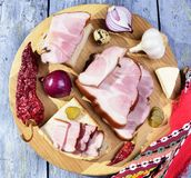 Smoked  bacon, pickles, onions ,garlic, paprika on a  wooden table - rustic style Stock Photo