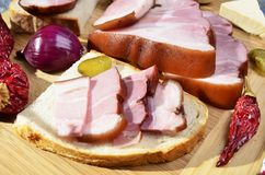 Smoked  bacon, pickles, onions ,garlic, paprika on a  wooden table - rustic style Stock Image