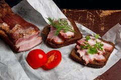 Smoked bacon with rye black bread and cuted tomatoes on the pack Stock Images