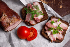 Smoked bacon with rye black bread and cuted tomatoes on the pack Stock Photo