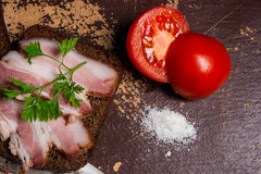 Smoked bacon with rye black bread and cuted tomatoes on the pack Royalty Free Stock Image
