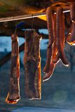 Smoked bacon and sausages hang on the bar. tasty traditional food royalty free stock photo