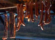 smoked bacon and sausages hang on the bar. tasty traditional food stock photography