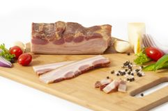 Smoked bacon slab on cutting board sliced with vegetables. Smoked bacon slab and slices on cutting board with vegetables isolated on white background royalty free stock image