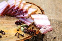 Smoked bacon, sliced on a wooden plank. stock image