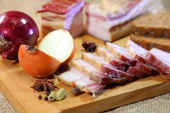 Smoked bacon, sliced on a wooden plank. stock images