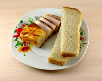 Smoked bacon and white bread. On a colorful plate Royalty Free Stock Photo