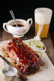 Smoked bbq baby back ribs paired with beer. On dark background Stock Photo